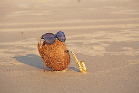 A coconut on the beach wearing sunglasses plays on a gold alto saxophone. Creative, humor and surrealism. Musical cover. Design with copy space.