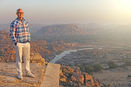 A handsome bald man in glasses stands at the top of a mountain and a temple in Hampi. A tourist man explores the Hampi territory at dawn. Solitary man. Vijayanagar, karnataka, unesco.