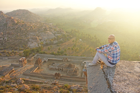 A handsome bald man in glasses sits on a sunset or dawn background in Hampi, on the top of the mountain. A brave man is extreme. India, Vijayanagar, karnataka, unesco. Stock Photo