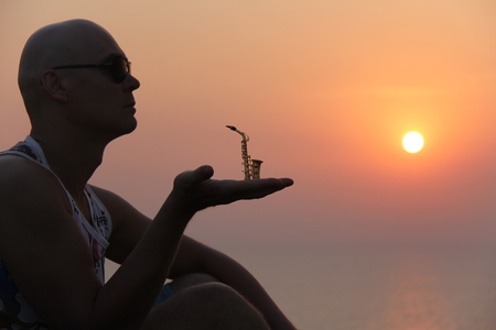 Male saxophonist at sunset. Alto saxophone at sunset. Silhouette of a mini saxophone.