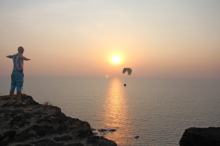 A paraglider against the background of the sea and sunset or dawn. Beautiful seascape. Extreme sport. The paraglider flies over the sea. India, Goa. Stock fotó