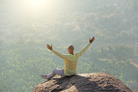 A young bald man raised his hands and greeted the sun on the top of the mountain against the background of sunrise or sunset. Relax, rest, alone with nature. Vijayanagar, karnataka, unesco.