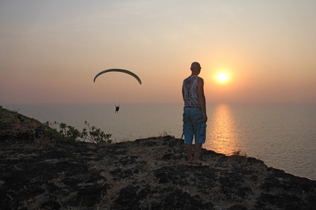 A man at sunset, standing on a cliff or at the top of a mountain, looking at the sun and dreaming of flying. The paraglider at sunset. The man lifted and opened his hands. India, Goa. Фото со стока