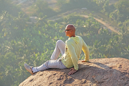 A young bald man sits on top of a mountain against a background of sunrise or sunset and looks afar, to the horizon. Relax, alone with nature. Meditation in nature. Vijayanagar, karnataka, unesco. Stock Photo