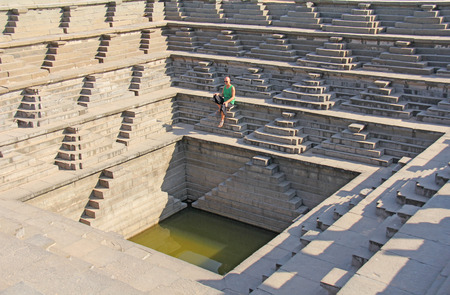 Royal enclosure in Hampi. A young bald man is sitting on the steps of the pool in Hampi. A solitary man is a thinker, thinks about the meaning of life. Vijayanagar, karnataka, unesco.