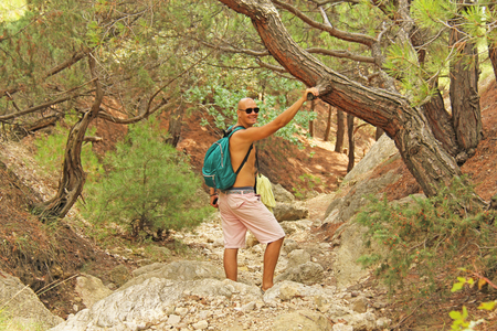 Young bald male tourist with a backpack on nature. Crimea. A beautiful mountain landscape.