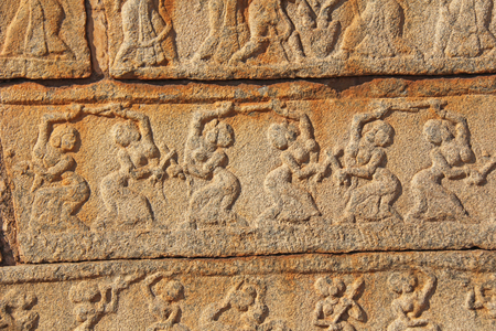 Stone bas-reliefs on the walls in Temples Hampi. Carving stone ancient background. Carved figures made of stone. Karnataka, India. Beige background. Royal enclosure.