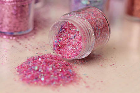 Pink Sequins for the design of nails in a box. Glitter in jars. Foil for nail service. Photo set. Sparkling beauty shimmer, glitter.