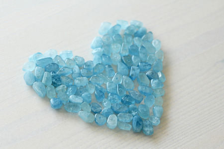 Aquamarine is blue. Blue heart. Natural stone is blue aquamarine. The background is aquamarine. Place for text. Card. Stockfoto