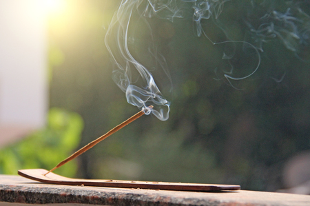 Incense stick and smoke from incense burning. Beautiful smoke. Blurred background and design with copy space. Stock Photo