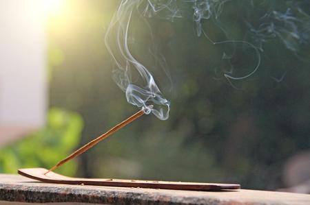 Räucherstäbchen und Rauch vom Weihrauchbrennen. Schöner Rauch. Verschwommener Hintergrund und Design mit Kopierraum. Standard-Bild