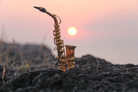 A golden alto saxophone against the background of the sun and sunset. Musical cover. Design with copy space. Stockfoto
