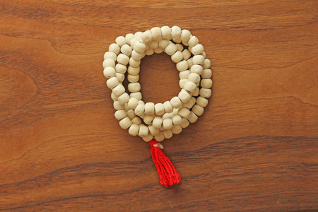 Buddhist beads. Rosary or beads from the sacred tree of Tulasi with a red tassel. Stock Photo