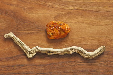 Amber and dry tree. Collection of natural rough stones on a natural wooden background made of black American walnut. Feng Shui, Zen, Relax.