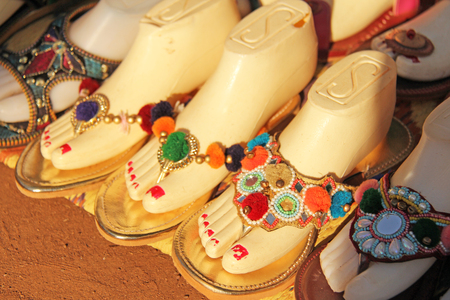 Ornaments on the foot. Shoes India is sold on the market in India. Gift souvenir India Tibet Bazaar.