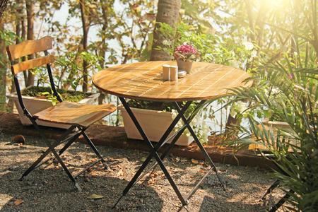 Café de verano. Mesa redonda de madera y silla al sol. El acogedor interior de la cafetería. Interior de madera.