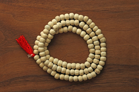 Buddhist beads. Rosary or beads from the sacred tree of Tulasi with a red tassel. 免版税图像