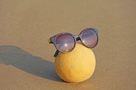 Yellow beautiful melon in glasses, on the beach and sea, against the background of sand. Asian natural and tropical fruits. Melon rests on the sea. Man is reflected in sunglasses. Fruit art and humor. Stock Photo