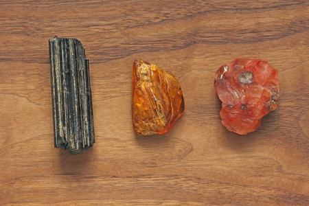 Black tourmaline, Sherl, Carnelian, Amber. Collection of natural stones of minerals on a background of natural wood American black walnut. Beautiful untreated stones and minerals, crystals.