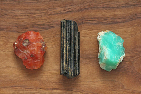 Black tourmaline, Sherl, Carnelian, Chrysoprase. Collection of natural stones of minerals on a background of natural wood American black walnut. Beautiful untreated stones and minerals, crystals. Stockfoto