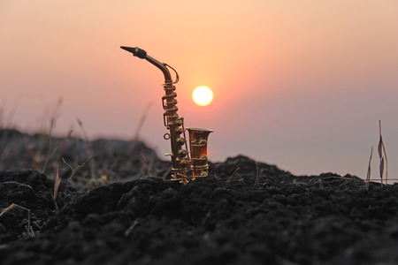 A golden alto saxophone against the background of the sun and sunset. Musical cover. Design with copy space. 写真素材