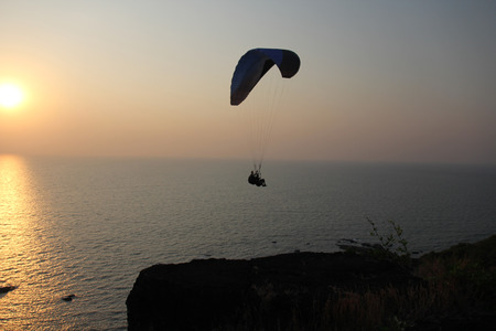 A paraglider against the background of the sea and sunset or dawn. Beautiful seascape. Extreme sport. The paraglider flies over the sea. India, Goa. 免版税图像
