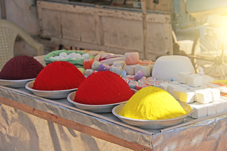 Bright multi-colored red and yellow powder for drawing mandalas on the ground. India, Hampi.