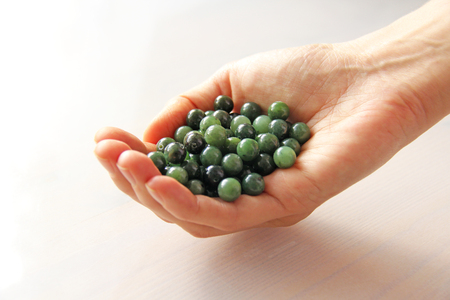 Natural green jade nephrite mineral stones beads. The green jade stone lies in the hands. Hands holding stone on white background. Green and grassy natural background made of round stone beads. 写真素材