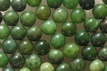 Natural green jade nephrite mineral stones beads. Green and grassy natural background made of round stone beads.