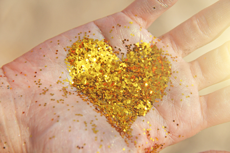 A golden shining heart lies in the hands of the girl. Golden heart. Design with copy space. Top view.