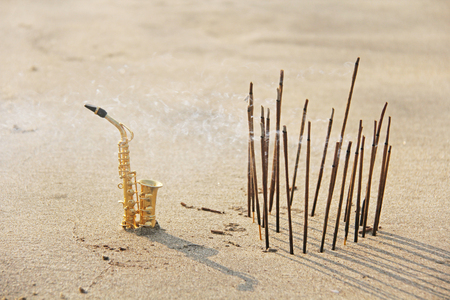 The golden alto saxophone stands on the sand next to the incense. Romantic musical background. Musical cover, creative, relaxation and meditation. Design with copy space.