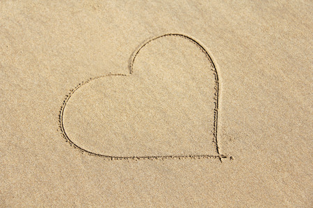 The heart is painted on the sand. Design with copy space. Top view. 写真素材