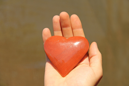 The hand holds a red or terracotta heart made of natural stone. Heart in hand. A stone in the shape of a heart. Love talisman, zen, spa.