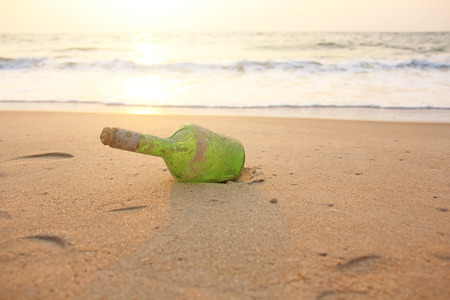 Green glass bottle with a message inside on the seashore on the beach against the backdrop of the sea and sunset. Magic and fairy tale. Design with copy space. Stock Photo