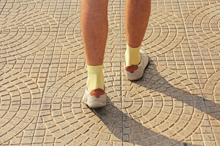 Men's Feet in Light Shoes and Yellow Socks Go along the Road. The island of Sicily, Italy. Men's Steps. Archivio Fotografico