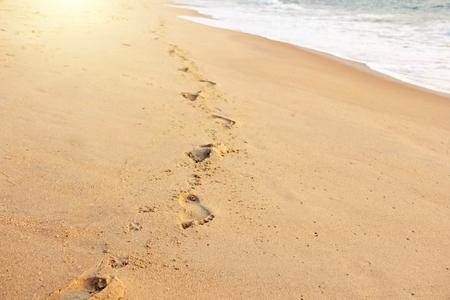 Ślady na piasku na tle morza. Miejsce na tekst. Projekt z miejscem na kopię.