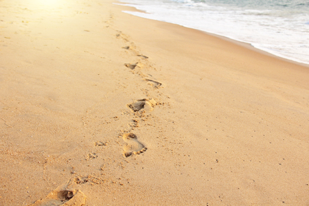Footprints in the sand against the background of the sea. Place for text. Design with copy space.