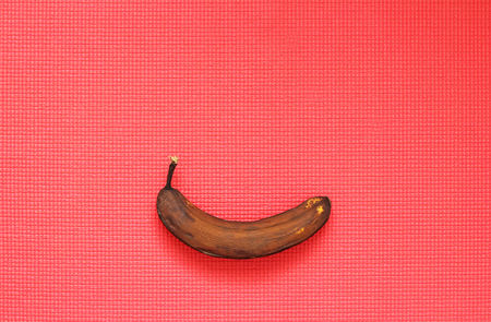 Black banana spoiled. A rotten banana on a bright red background, pop art. Single spoiled black banana. Copy space for your text. Trendy spoiled organic fruits - Image.