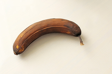 Black banana spoiled. A rotten banana on a white wooden background, pop art. Single spoiled black banana. Copy space for your text. Trendy spoiled organic fruits - Image.