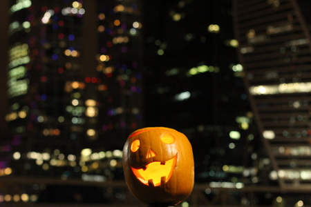 Halloween Pumpkins head. Orange pumpkin with a smile and eyes on night city and lights background.