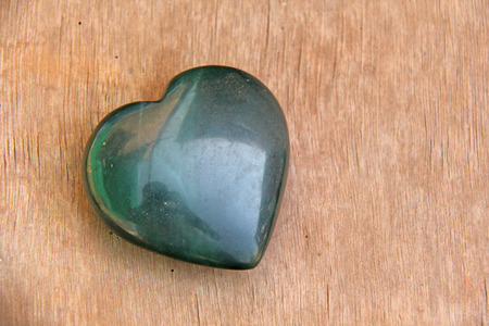 Green heart made of natural stone jade. A heart shaped stone lies on a brown or beige background. Love talisman, zen, spa. Imagens