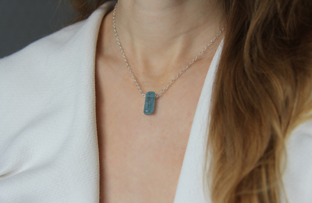 Crystal blue aquamarine beryl on a silver chain on the girl. Pendant aquamarine, pendant, decoration on the neck. Natural blue aquamarine. Minimalism, Zen. Copy space for your text. Imagens