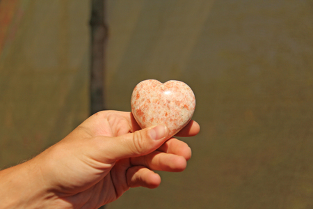 The hand holds the heart from natural stone rhodochrosite. Heart in hand. A stone in the shape of a heart. Love talisman, zen, spa. Stock Photo