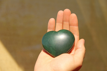 The hand holds the heart from natural stone green jade. Heart in hand. A stone in the shape of a heart. Love talisman, zen, spa.