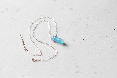 Berilo aguamarina azul cristal en una cadena de plata. Colgante aguamarina, colgante, decoración en el cuello. Aguamarina azul natural sobre un fondo gris. Minimalismo, zen. Copie el espacio para su texto.
