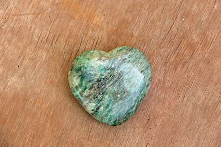 Green heart made of natural stone marble. A heart shaped stone lies on a brown or beige background. Love talisman, zen, spa. Stock Photo