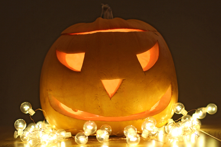 Halloween Pumpkins head. Orange pumpkin with a smile and glowing eyes. Neon.