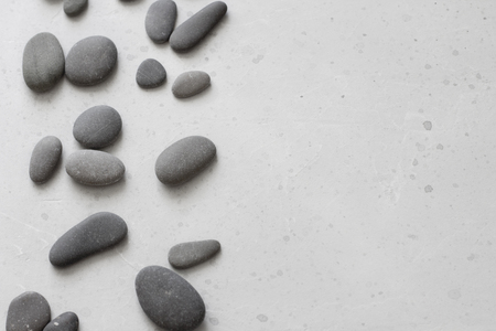 Spa background with grey stones, gray modern background, cover, template with round gray stones, flat lay. Copy space for your text. Stones scattered on a gray background.