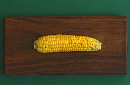 Delicious boiled corn. Corn on cob on rustic wooden table and wooden background from a natural wooden. Golden bright yellow corn. Tasty and healthy food.