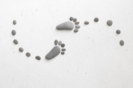 Footprints made of stones. Happy feet. Stone arranged like footprints on the beach. Spa background with grey stones. Copy space for your text. Aromatherapy for beauty, relaxation, nature massage. 스톡 콘텐츠